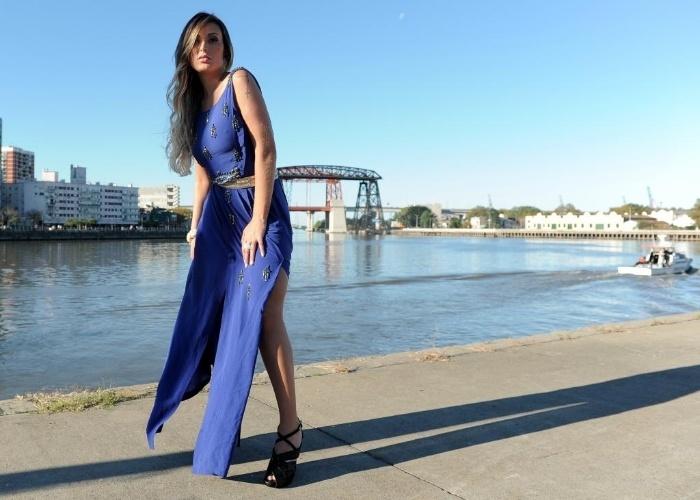 23.abr.2013 - A modelo Andressa Urach, ex-namorada do cantor Latino e vice campeã do Miss Bumbum 2012, posou com um vestido azul esvoaçante com uma fenda que exibe as pernas da beldade. As fotos foram feitas no bairro turístico de Puerto Madero, na capital da Argentina