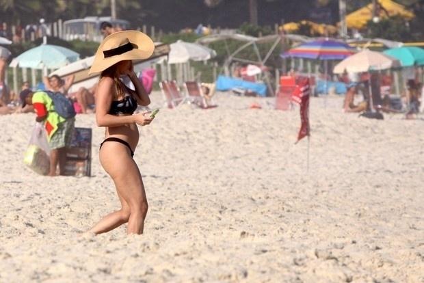 """4.mai.2013 - Danielle Winits exibiu uma barriguinha suspeita na praia da Barra da Tijuca, no Rio. Segundo informações do site """"Ego"""", a assessoria da atriz negou possível gravidez da global"""