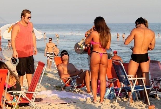 """4.mai.2013 - Esbanjando sensualidade, Nicole Bahls causou alvoroço na praia do Pepê, na Barra da Tijuca, zona oeste do Rio. A modelo chamou atenção pelas curvas generosas em um microbiquíni. A beldade estava acompanhada do ex-BBB Diego Alemão (regata laranja) e do juiz de futebol Diogo Pombo, com quem ficou confinada em """"A Fazenda 5"""" (2012)"""