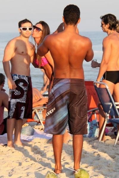 4.mai.2013 - Esbanjando sensualidade, Nicole Bahls causou alvoroço na praia do Pepê, na Barra da Tijuca, zona oeste do Rio. A modelo chamou atenção pelas curvas generosas em um microbiquíni. Na imagem, Nicole posa com um fã