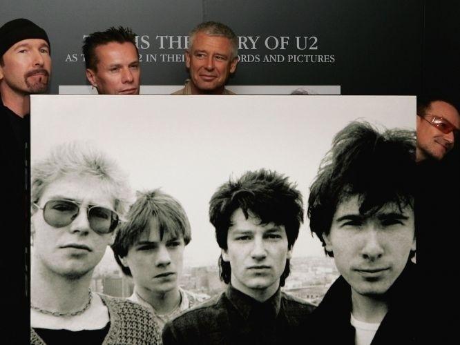 """22.set.2006 - The Edge, Larry Mullen Jr, Adam Clayton e Bono posam com foto do U2 no começo da carreira em evento de lançamento do livro """"U2 by U2"""", em Londres, Inglaterra"""