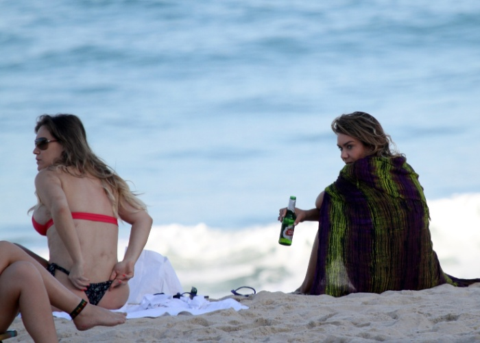 """20.mai.2013 - A atriz e apresentadora Luize Altenhofen aproveitou o sol do Leblon para retocar o bronzeado. A gata, que está na novela global """"Amor à Vida"""", em que interpreta uma instrutora de mergulho, já deu entrevistas avisando que, por causa da ascendência alemã, adora beber cerveja e, em seu passeio na praia no Rio, esteve acompanhada por uma garrafa. Mas pelo jeito a bebida não está atrapalhando a dieta de Luize, que exibiu curvas invejáveis"""