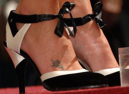 Charlize Theron tem uma flor bem pequenina no pé direito