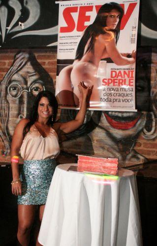 Dani em frente a pôster de sua capa de revista.