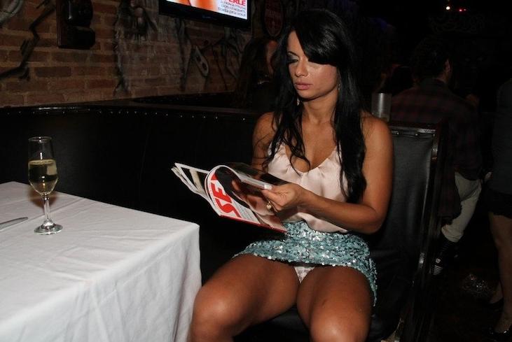 A bela folheia as páginas da revista que traz seu ensaio nu e, aparentemente sem querer, exibe a calcinha.