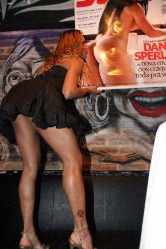 A modelo Alessandra Matos posa ao lado do pôster de Dani Sperle.