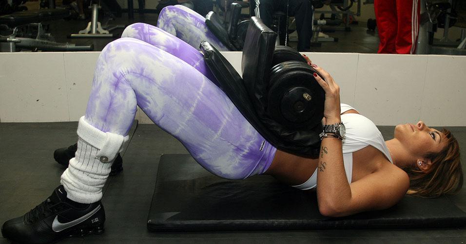 Ela sobe e desce o quadril sem tirar a parte de cima das costas do chão. Ela usa um colchonete dobrado para apoiar o peso sem se machucar.