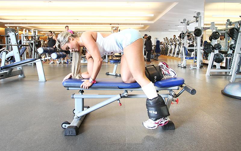 O segundo exercício de glúteos da loira é o quatro apoios com perna estendida em cima do banco. Uma das pernas começa para baixo do banco, próxima do chão