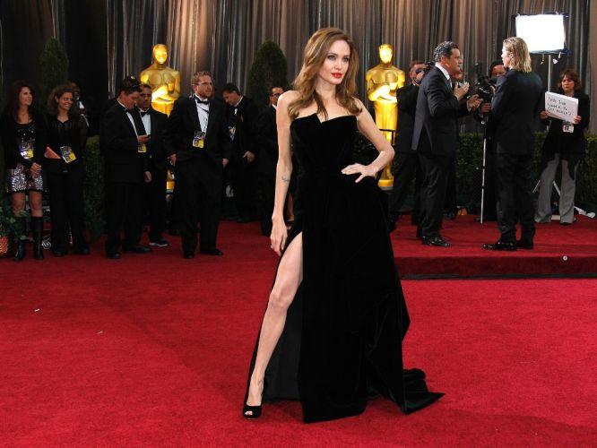 Segunda-feira (27/2) - Com cabelo mais claro, batom vermelho e fenda que revelava uma das pernas praticamente inteira, Angelina Jolie arrancou suspiros de todos em sua rápida passagem usando um tomara-que-caia assimétrico no busto assinado pela Atelier Versace na festa do Oscar do domingo (26/2).